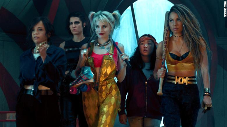 Image still from Birds of Prey- The cast of the film, Margot Robbie, Jurnee Smollett, Rosie Perez, Mary Elizabeth Winstead, and Ella Jay Basco, are standing in costume waiting to face off the bad guys.