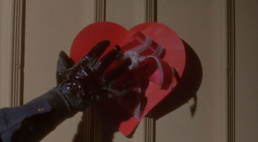 Image still from My Bloody Valentine- A hand is covering a red heart decoration on a door