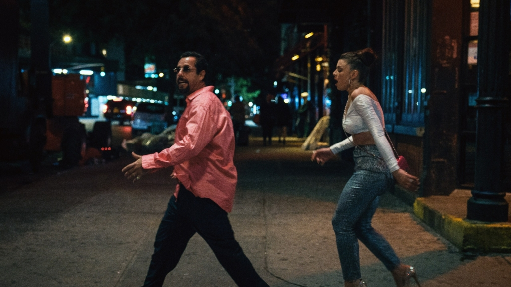 Image still from Uncut Gems- Howie (Adam Sandler) is walking as his girlfriend Julia Fox walks behind him upset.