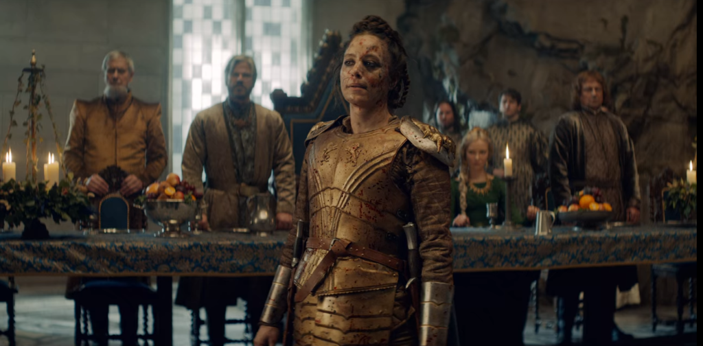 Image still from The Witcher- Queen Calanthe (Jodhi May) standing in the middle of a dining hall, dressed in gold armor.