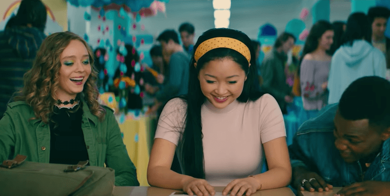 Image still from To All The Boys: P.S. I Still Love You- Lara Jean (Lana Condor), Chris (Madeleine Arthur), and Lucas (Trezzo Mahoro) laughing at lunch together
