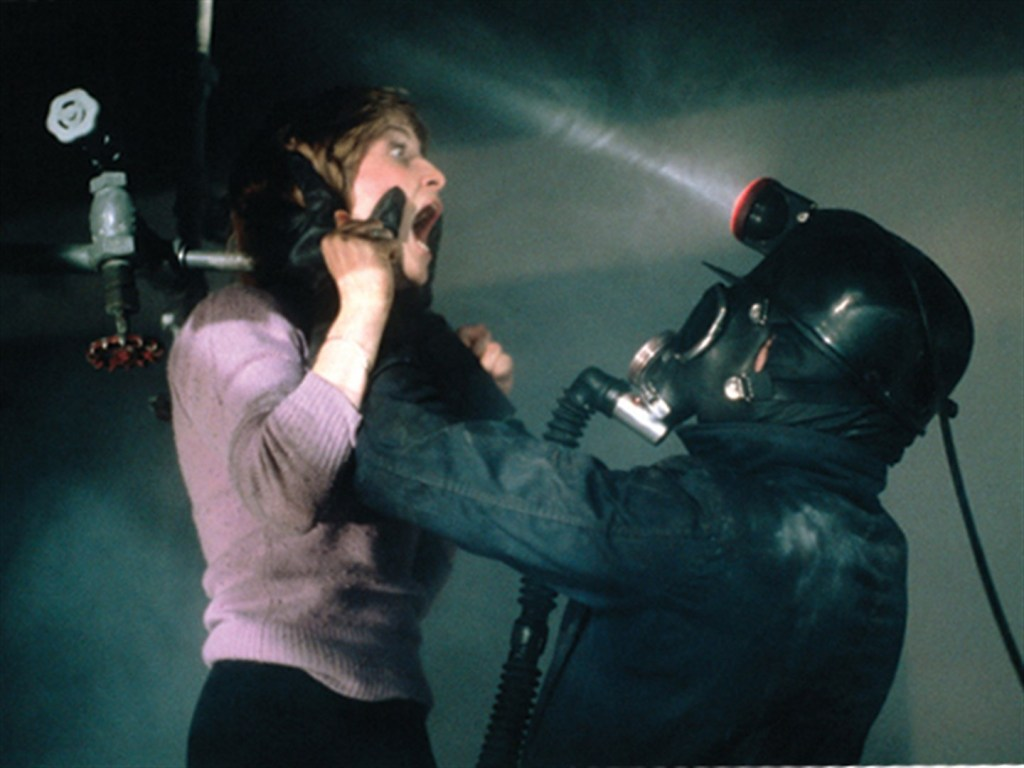 Image still from My Bloody Valentine- A woman is being held up by a masked villain in a miner's costume