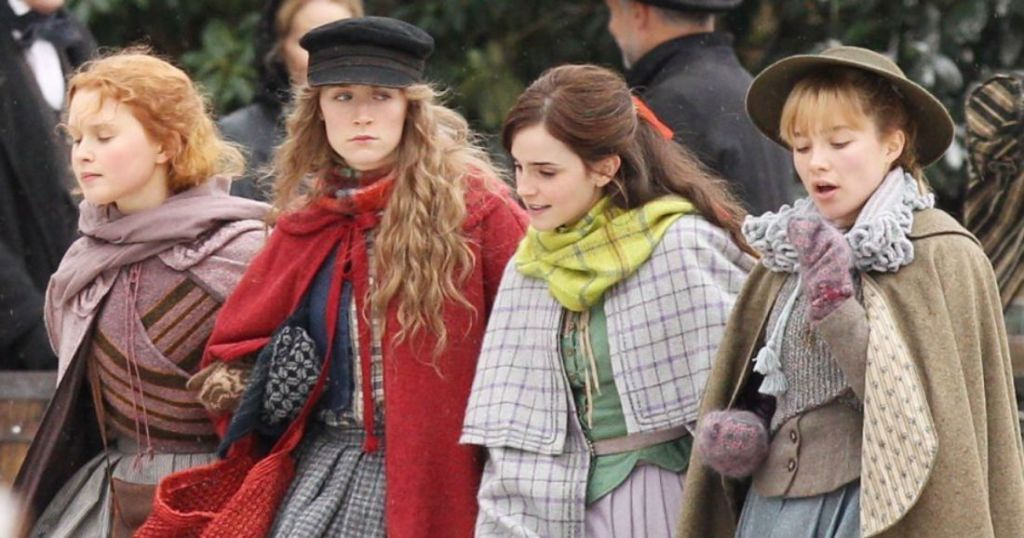 Image still from Little Women- Jo (Saoirse Ronan), Amy (Florence Pugh), Meg (Emma Watson), and Beth (Eliza Scanlon) are sisters walking arm-linked through the town.