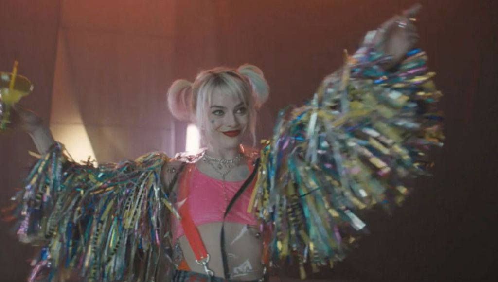 Image still from Birds of Prey- Harley Quinn (Margot Robbie) dancing with a margarita in her hand, dressed in a colorful outfit