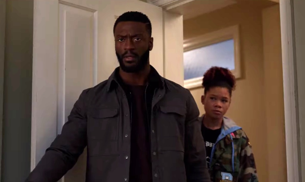 Image still from Invisible Man- Aldis Hodge and Storm Reid are standing in a door way, looking at something off camera.