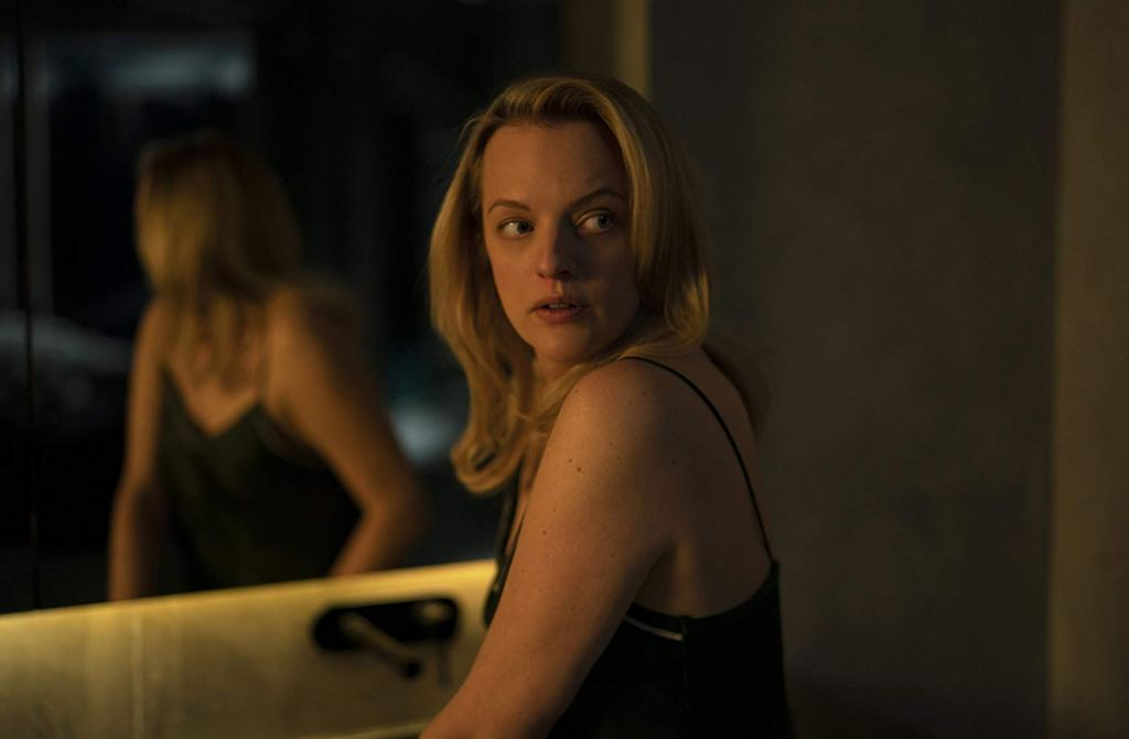 Image still from Invisible Man- Cecilia (Elizabeth Moss) is standing in front of a mirror looking over her shoulder.