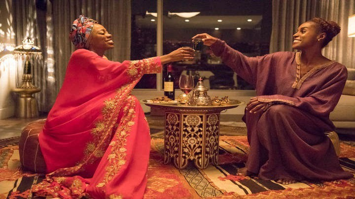 Image still from Insecure- Molly (Yvonne Orji) and Issa (Issa Rae) are having dinner together on the living room floor. They're sharing a toast.