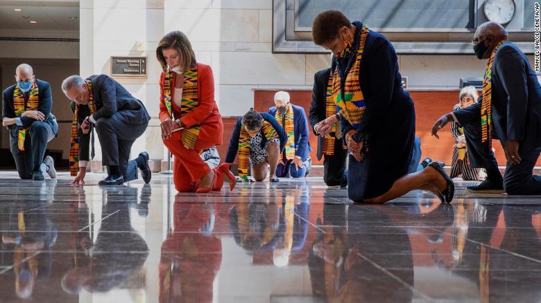 Dems kneeling in Kente cloth.