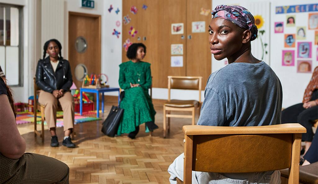 Image still from I May Destroy You- Michaela Coel is sitting in group therapy, looking back at the camera